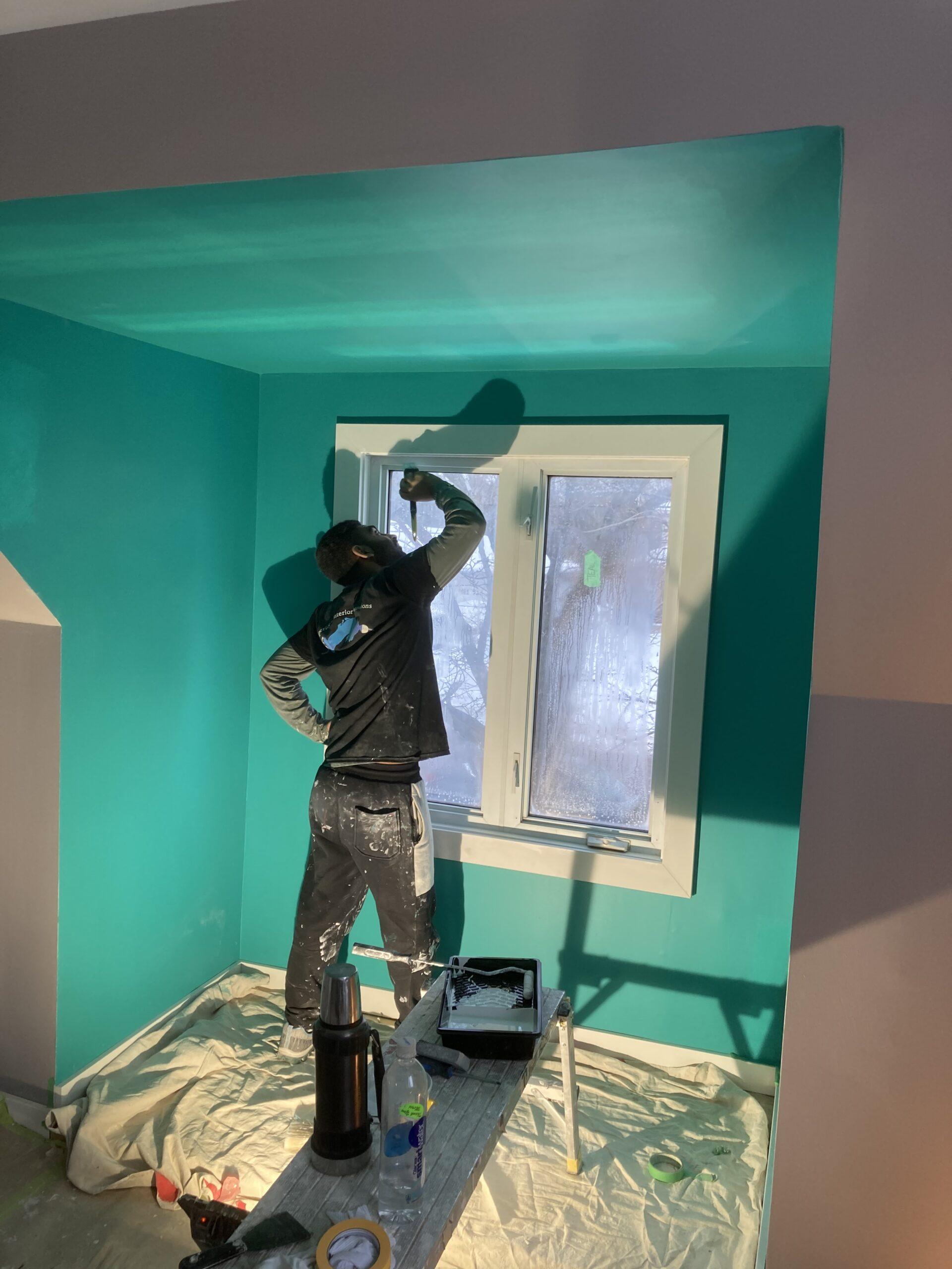 employee painting window trim